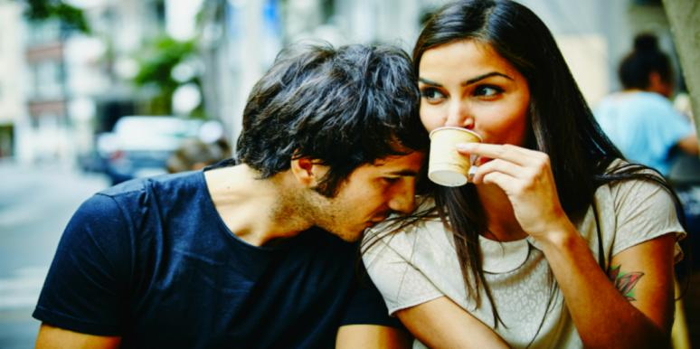 woman sipping from cup with man resting head on her shoulder
