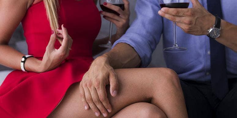 couple drinking wine man's hand over woman's leg
