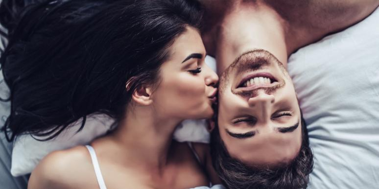 woman kissing a man in bed
