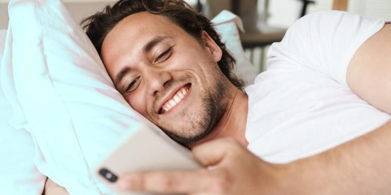 man laying in bed smiling at his phone