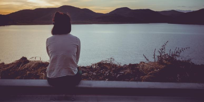 woman sitting looking out at a pretty landscape