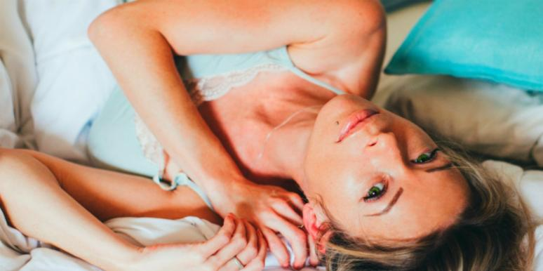 Woman lying back in bed, looking at the camera in a sexy way