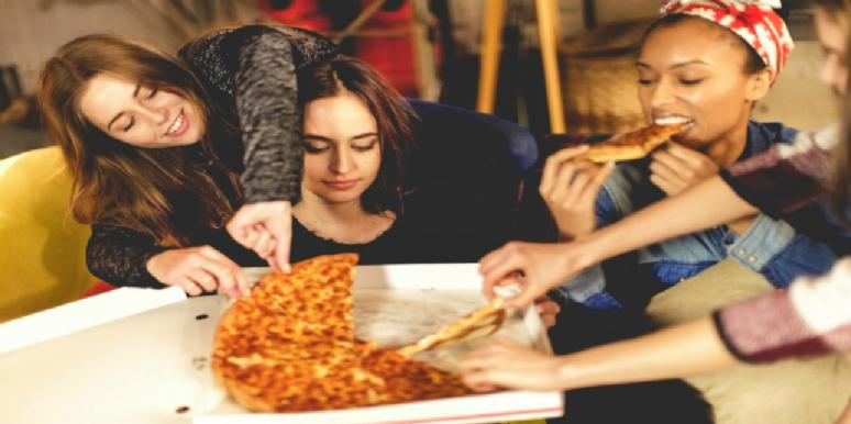 sad girl eating pizza with friends