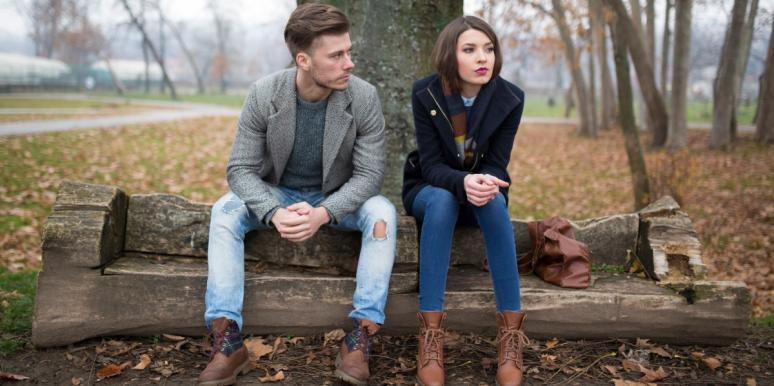 solemn couple sitting on bench