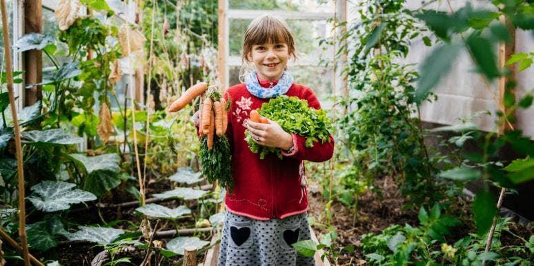 smiling girl holding carrots