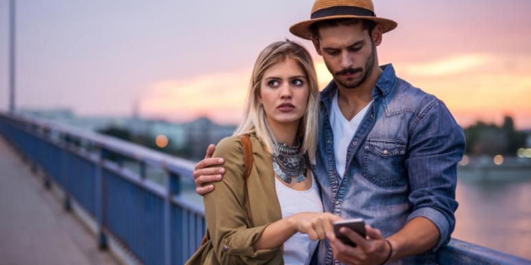 man looking on phone with woman