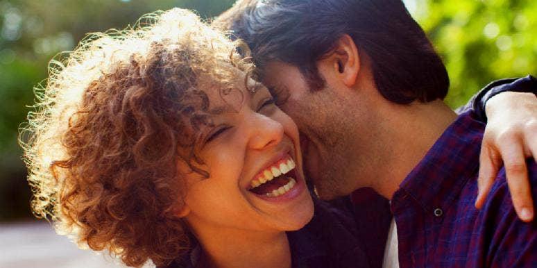 smiling girlfriend hugging her boyfriend