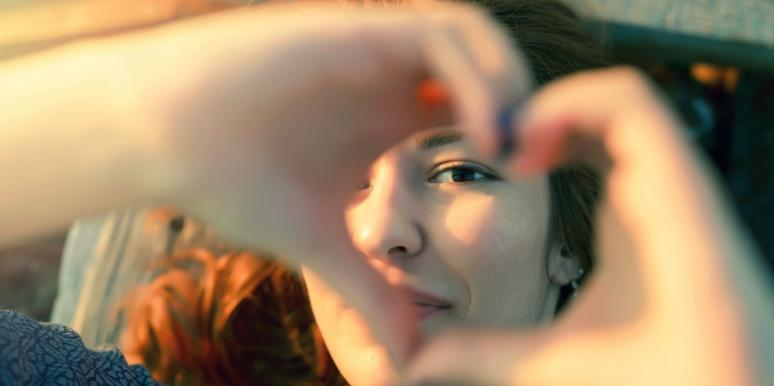 happy woman making heart shape with hands