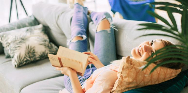 white woman lounges on couch with book trying to transform life