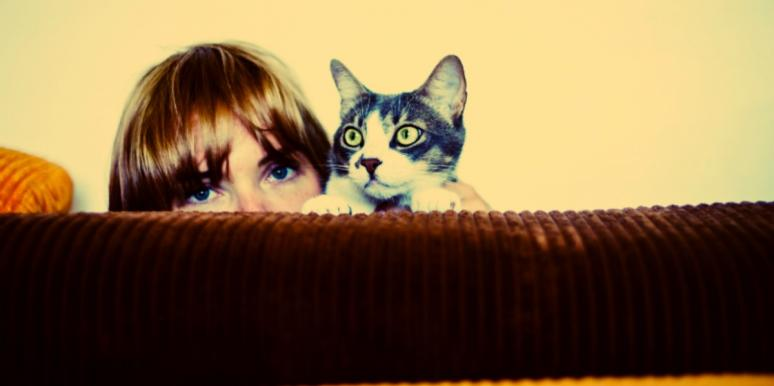 woman with long blonde bangs hides behind couch with her cat