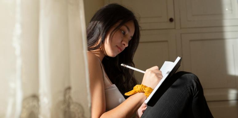 woman writing on a journal