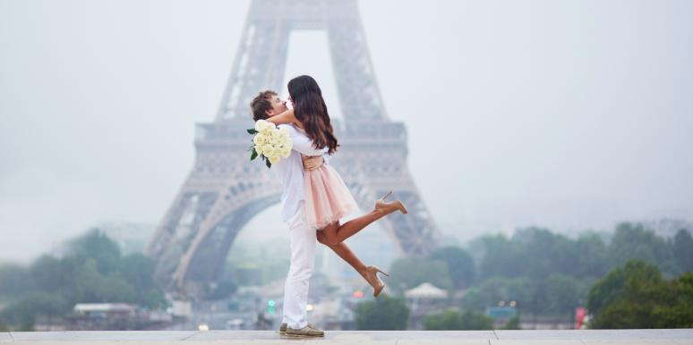 man with woman in his arms in front of the Eiffel tower