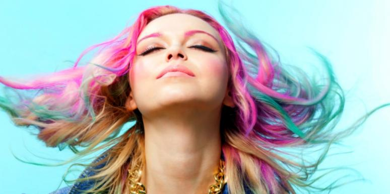 woman with colored hair blowing blue background
