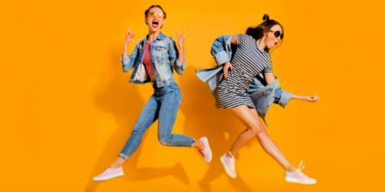 two girls happy jumping yellow background