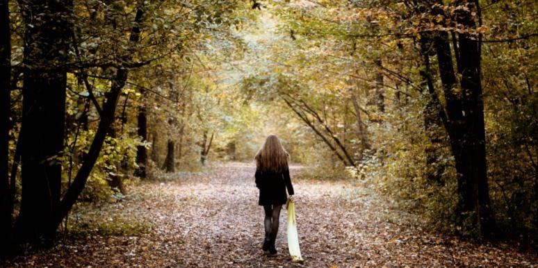 woman walking away in forest