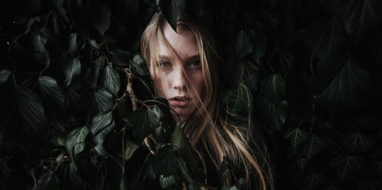 woman with a life out of balance hiding behind leaves