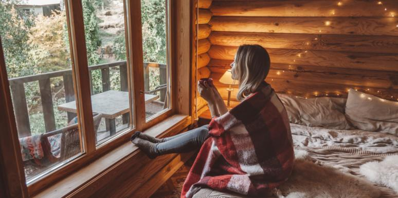 woman with coffee blanket cabin looking out window