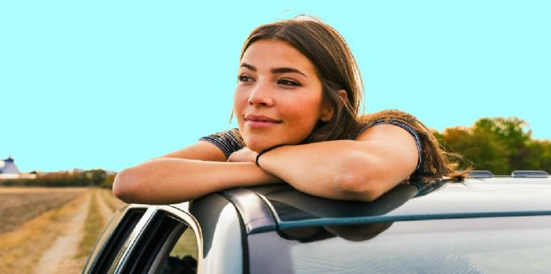 smiling woman looking out of car window
