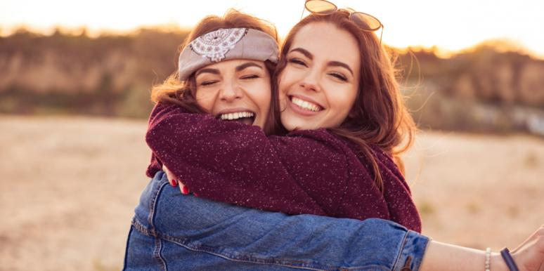 two friends smiling hugging