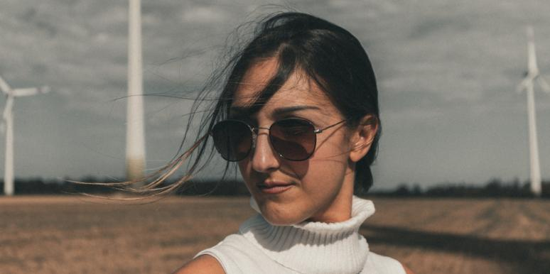 woman with sunglasses standing in field