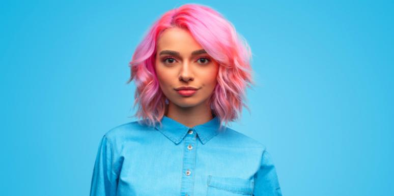 blue background woman in blue shirt pink hair