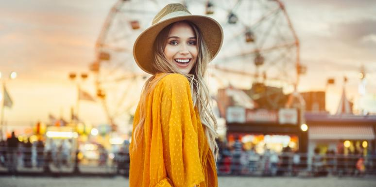happy woman standing in front of a ferris wheel