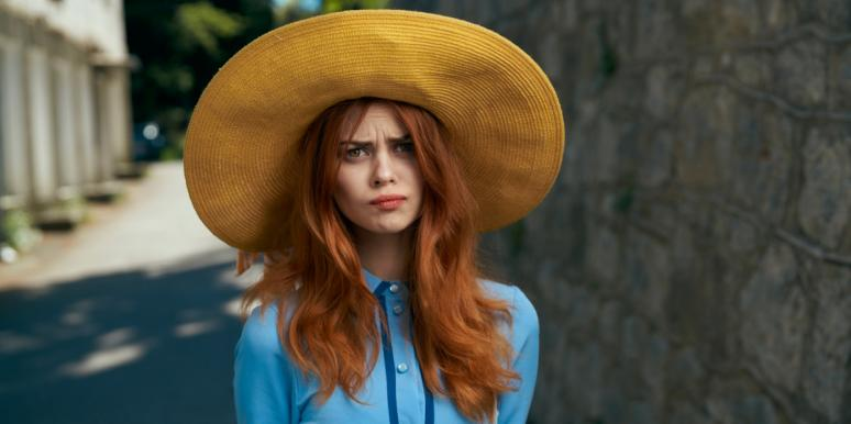 woman in a hat looking concerned