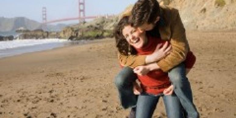 couple on the beach in san francisco goldeen gate bridge