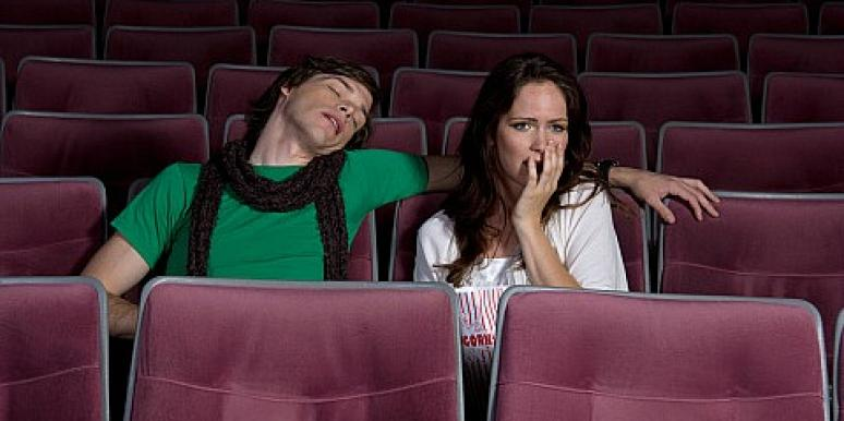 man asleep in movie theater while woman watches movie