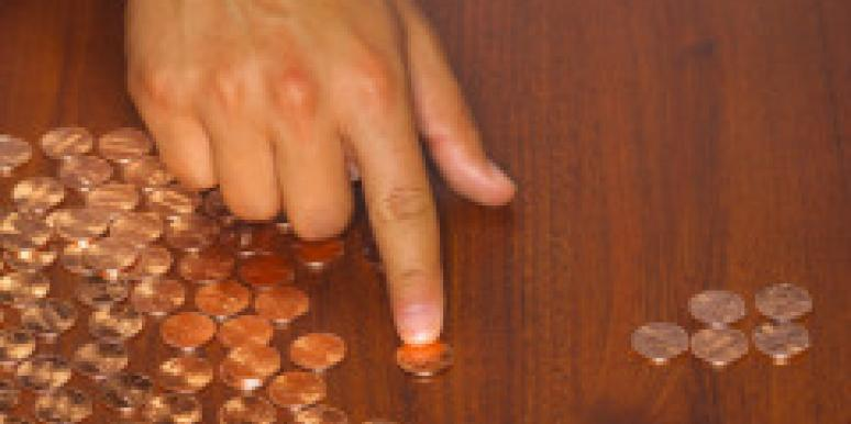 man counting pennies with hand on wood table