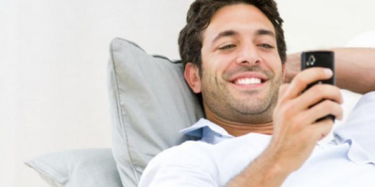 Man smiling while looking at the phone