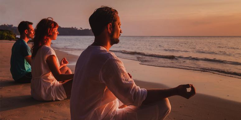 Men and women meditating on the beach