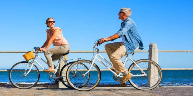 older man and woman biking