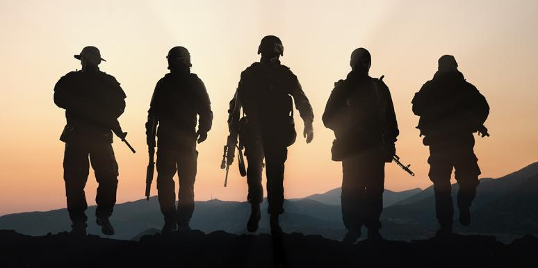Silhouette of military members against a sunset
