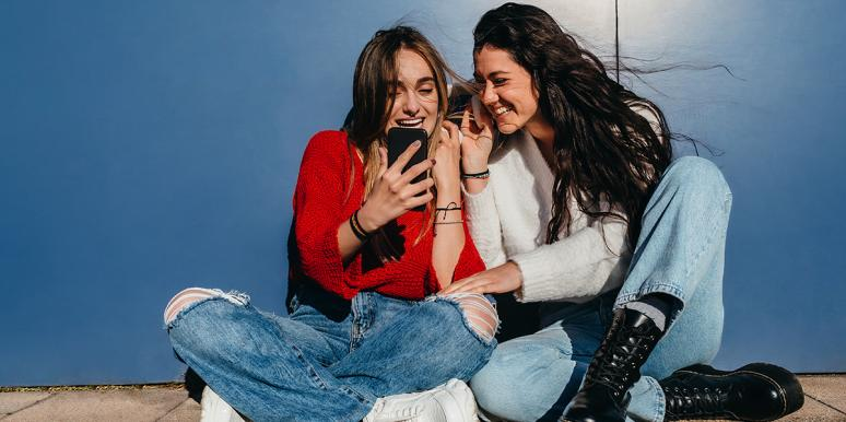 young girls looking at the phone laughing