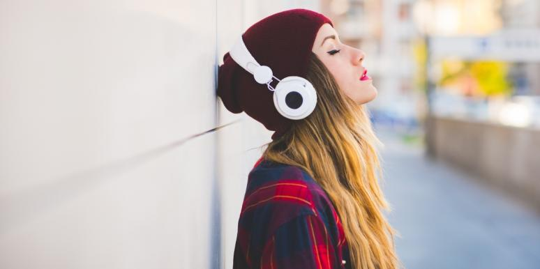 woman wearing beanie and headphones leaning on wall