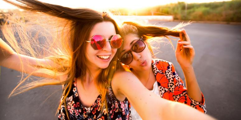 two friends in sunglasses smiling laughing