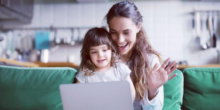 woman with little girl on her lap waving at a computer
