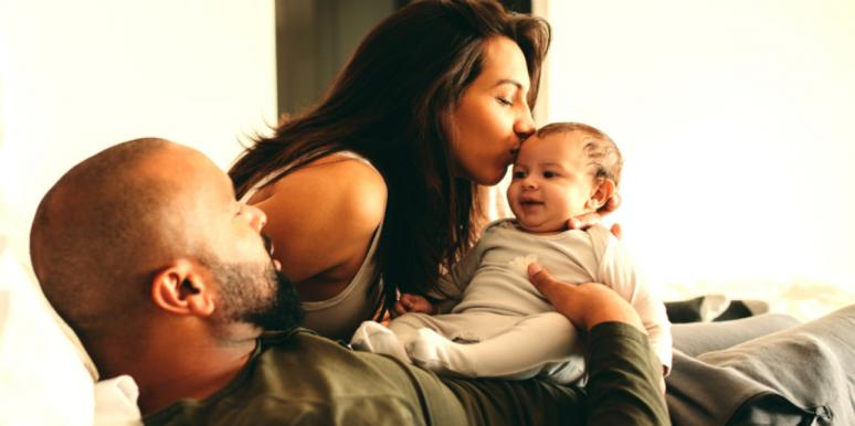 man woman and baby happy in bed