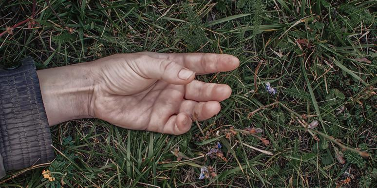 Hand of dead person in grass