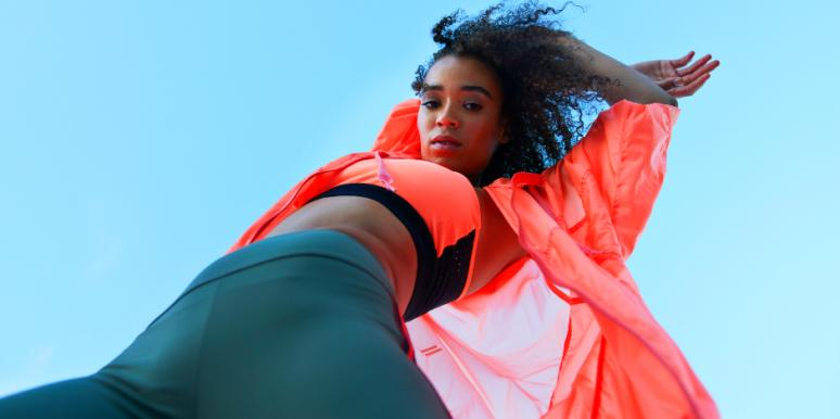 upward-facing shot of a young athletic Black woman in an orange top