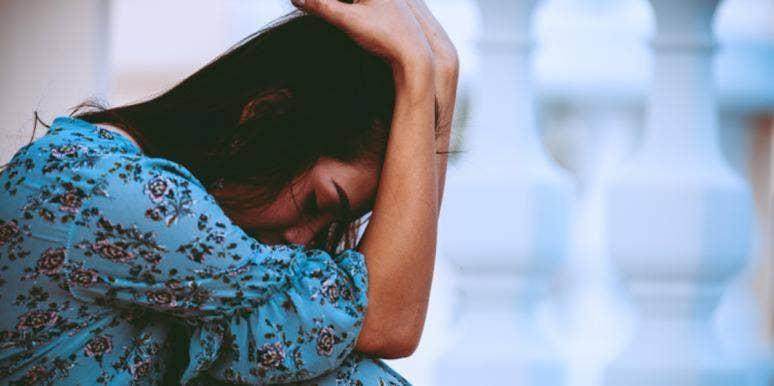 woman in blue dress head in her hands
