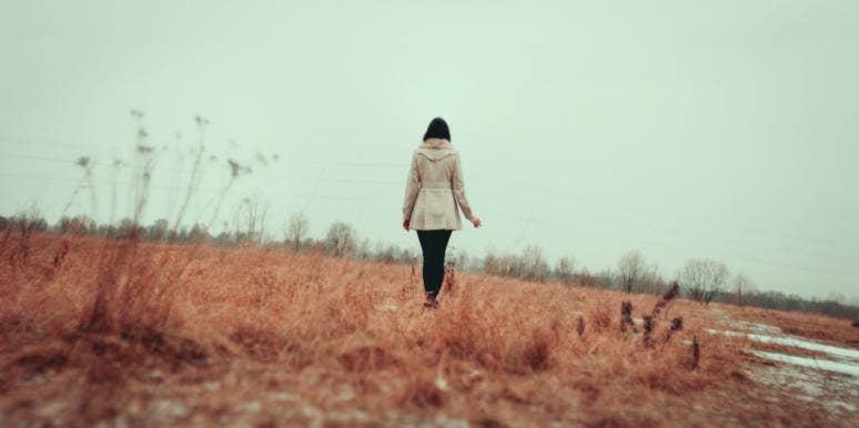 woman in a field walking away