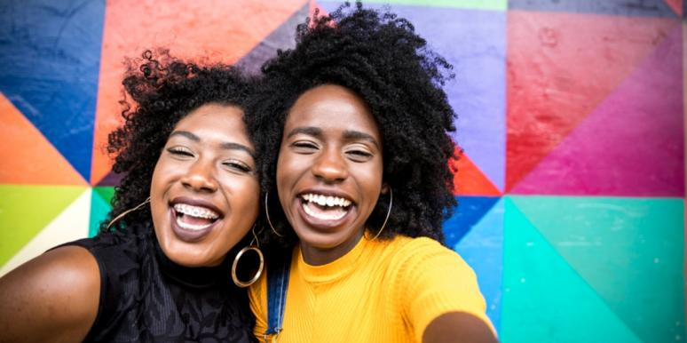 two Black women smiling in front of a colorful background