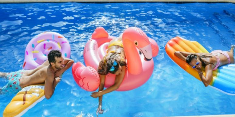 friends swimming in the pool with floaties