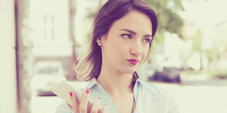 annoyed looking woman holding a smartphone