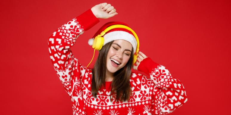 woman dancing in christmas sweater and headphones