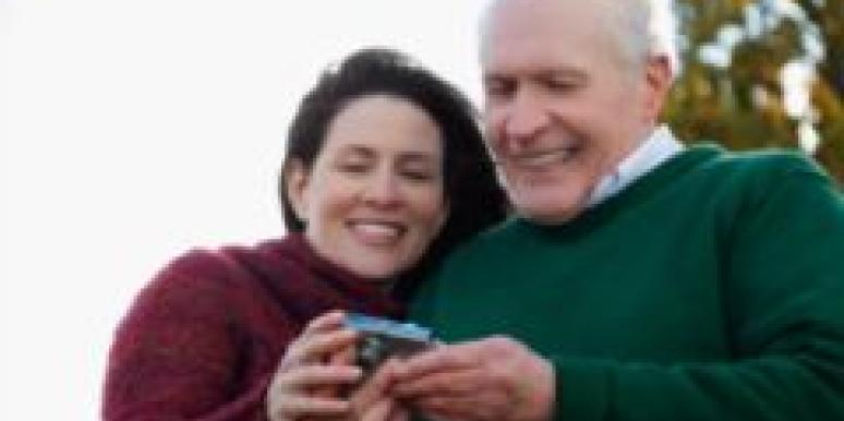 older happy married couple looking at photos