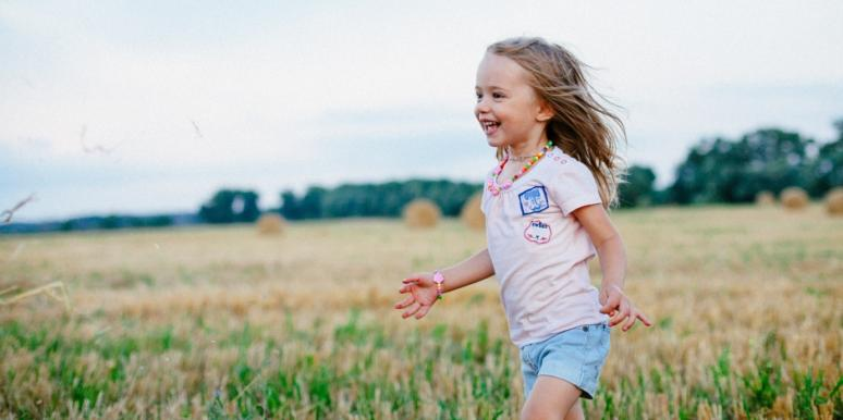 Child running through field