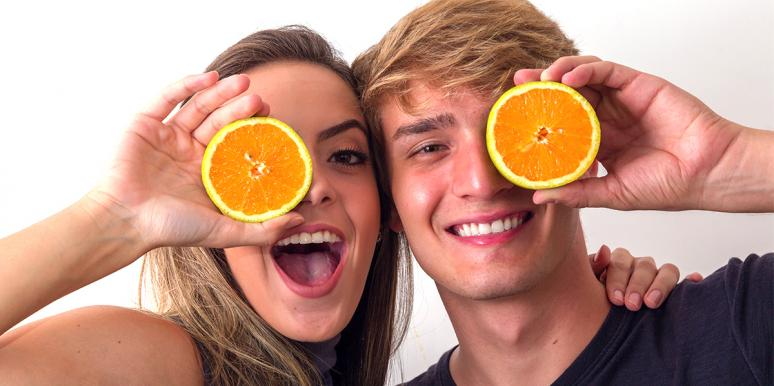 Young blonde woman and young blonde man holding oranges over their faces